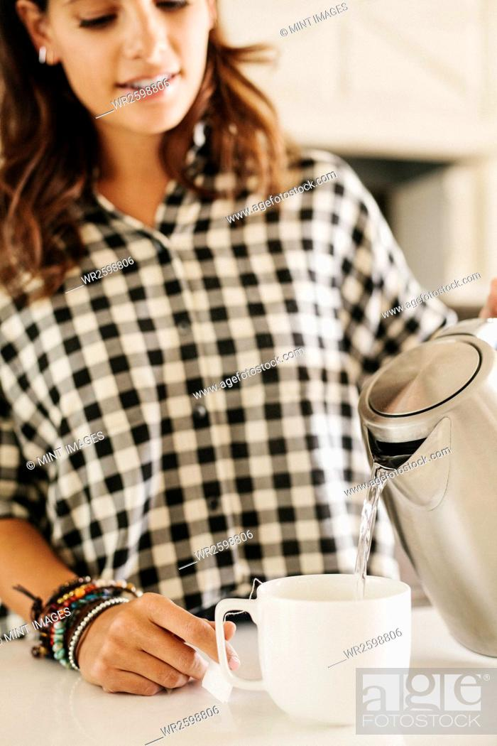 Stock Photo: Woman with long brown hair, wearing a chequered shirt, making a cup of tea.