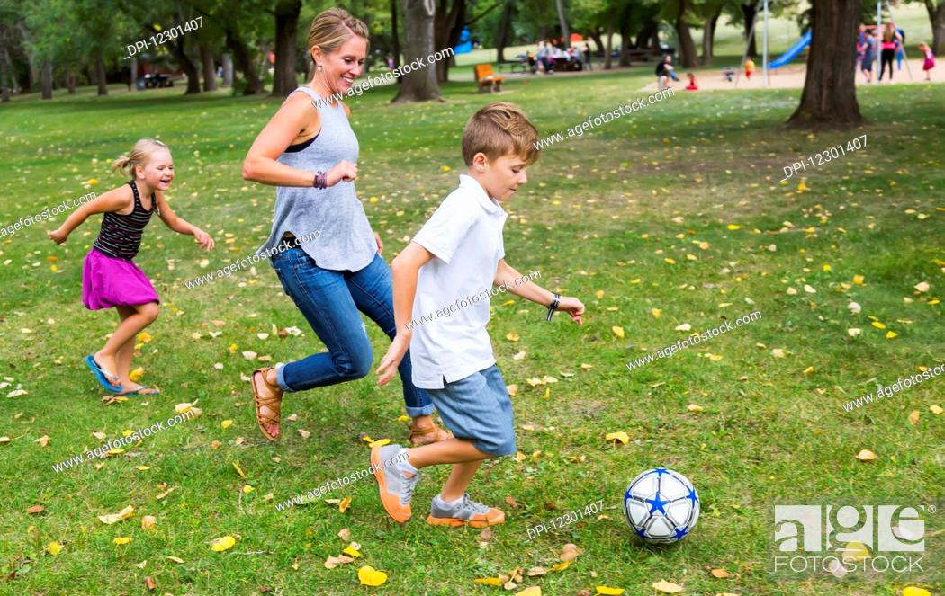 Photo de stock: A mother playing soccer with her kids in a park during a family outing; Edmonton, Alberta, Canada.