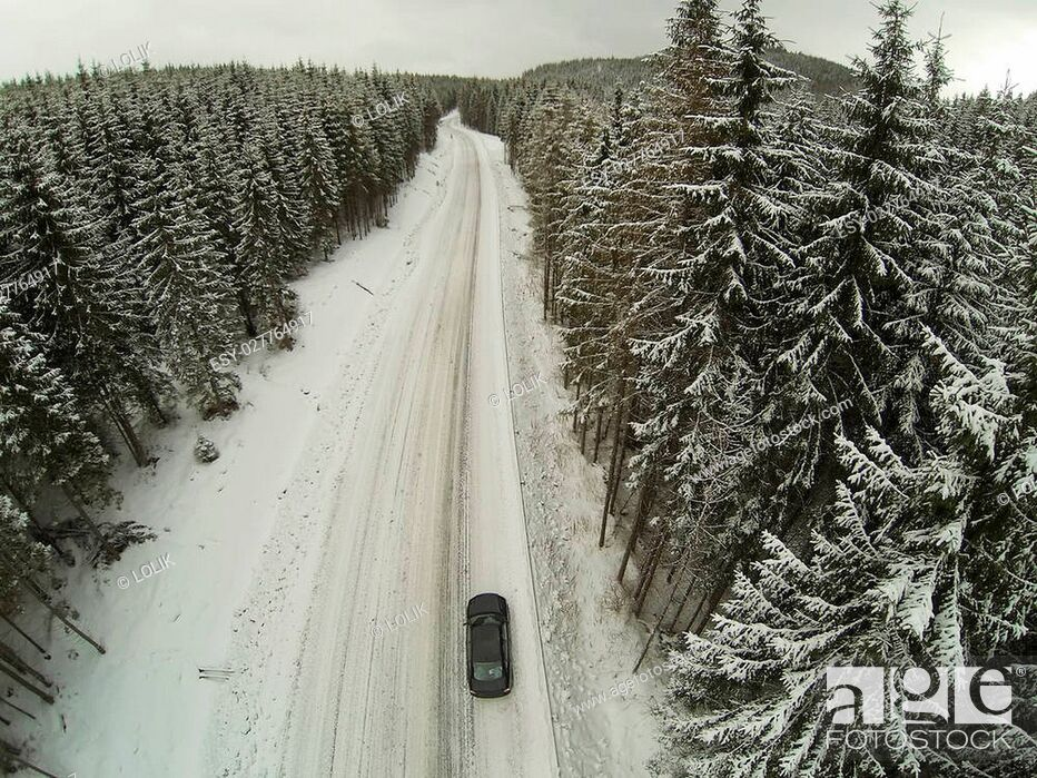 Stock Photo: Aerial shot of snow-covered road in the countryside Carpathian Mountains with car on way.