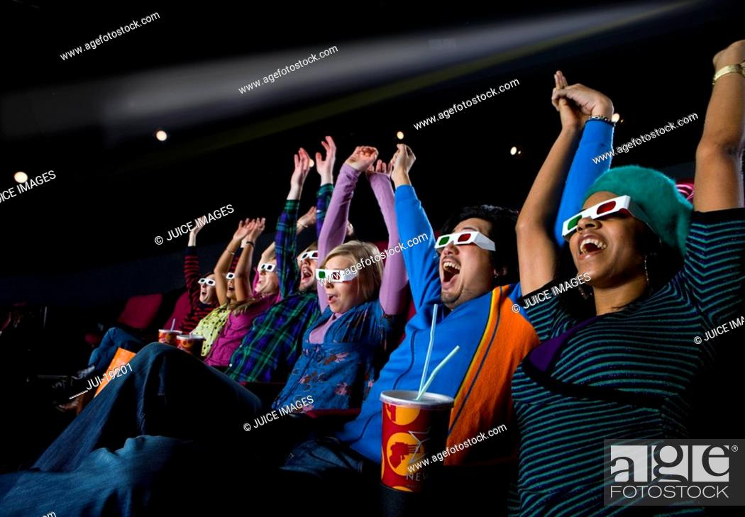 Stock Photo: Audience in cinema wearing 3D glasses, arms raised, low angle view.