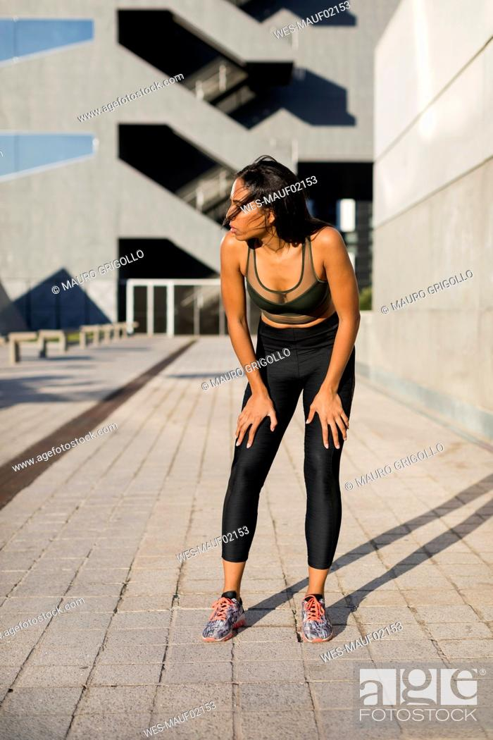 Stock Photo: Sporty young woman having a break during workout in the city.