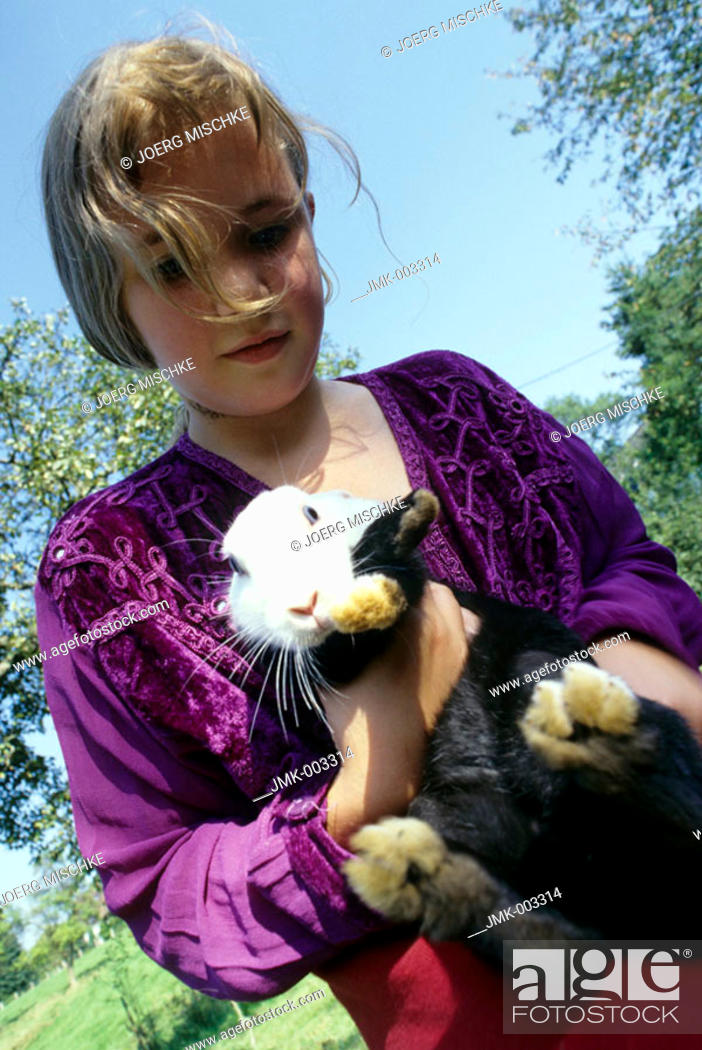 Stock Photo: A girl, 5-10 years old, holding a rabbit, bunny, on it's arms.