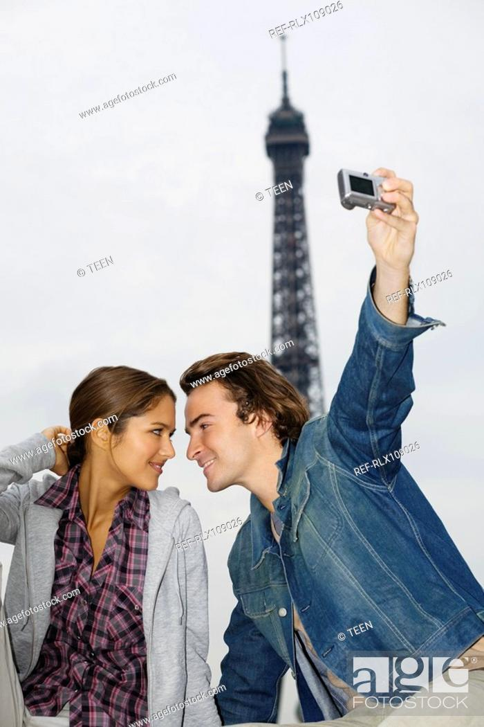 Stock Photo: Young couple, man taking photo with digital camera, Eiffel tower in background.