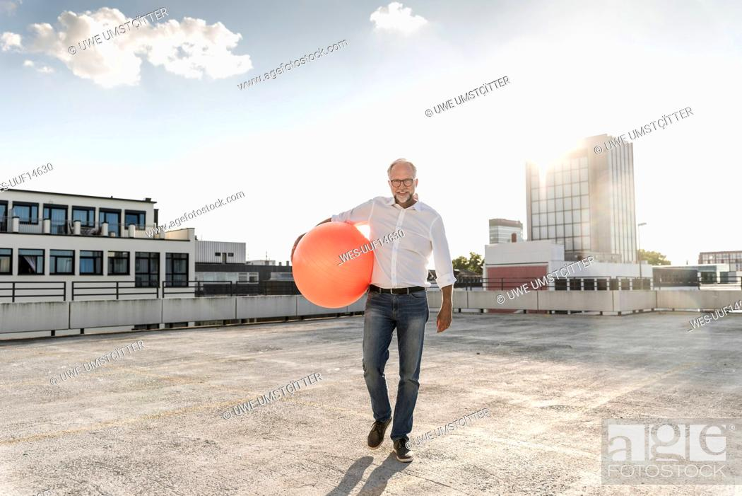 Stock Photo: Mature man playing with orange fitness ball on rooftop of a high-rise building.