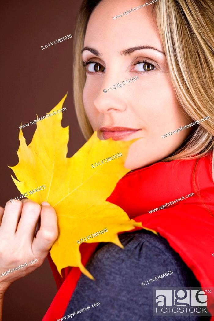 Stock Photo: A mid adult woman holding an autumn leaf.