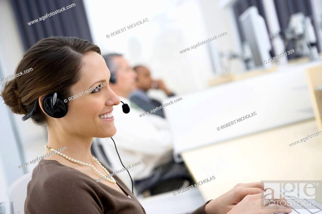 Stock Photo: Smiling businesswoman wearing headset in office.
