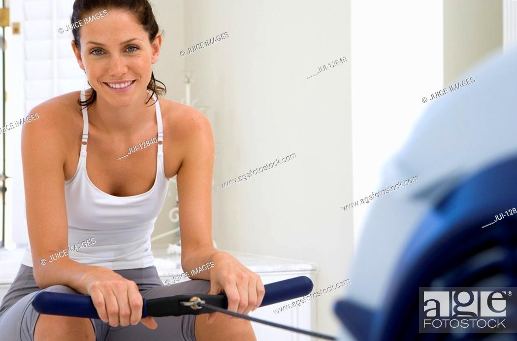 Stock Photo: Young woman on exercise machine, smiling, portrait.