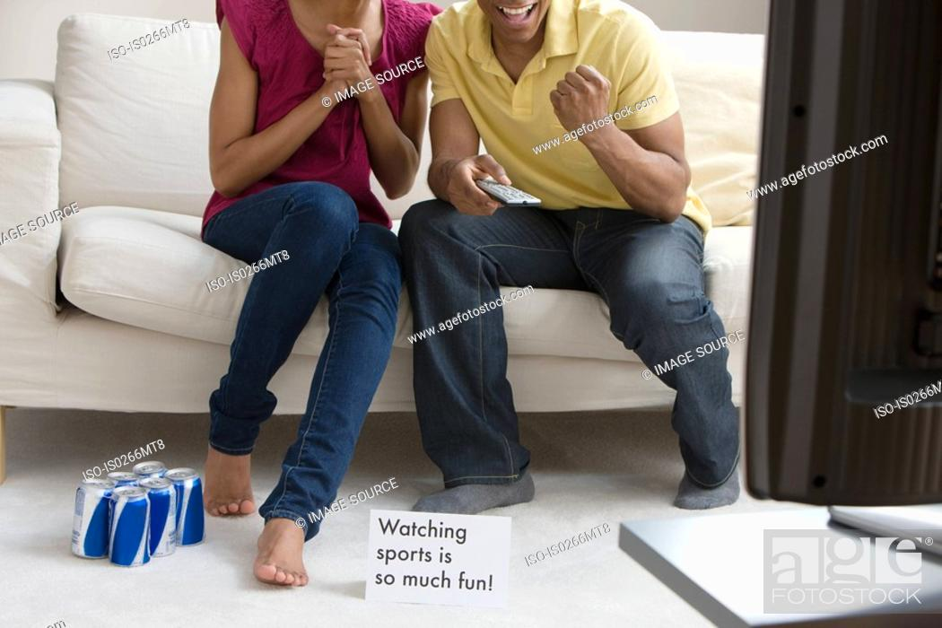 Stock Photo: A couple watching sport on the tv.