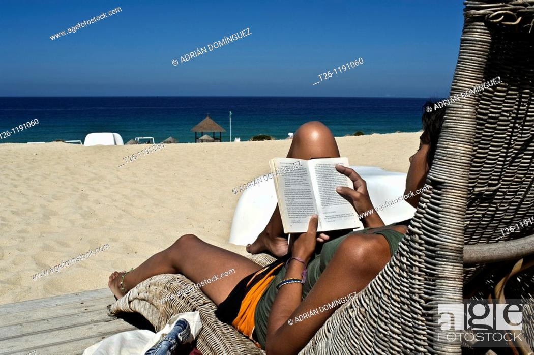 Stock Photo: A woman reads relaxed in a chair facing the sea. Alentejo, Portugal.