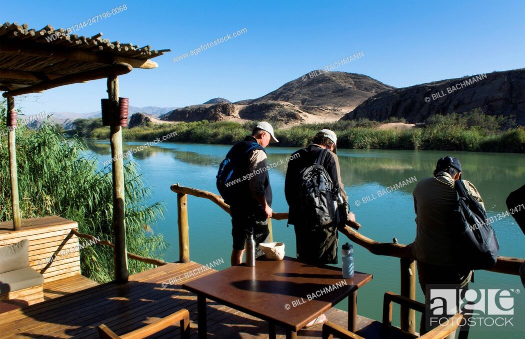 Imagen: Namibia Africa three tourists looking at Kunene River from resort of Serra Cafema Camp resort looking at Angola across river in safari vacation.