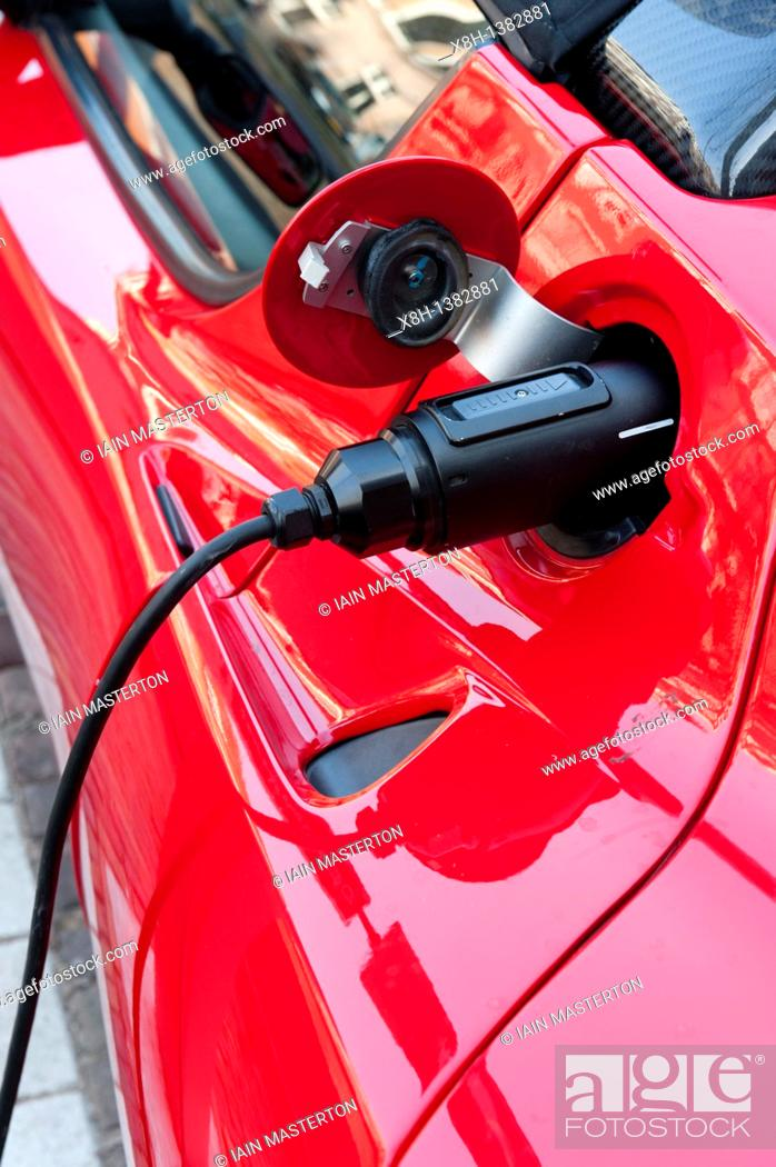 Stock Photo: Electric Tesla sports car being recharged at public recharging point in Amsterdam The Netherlands.