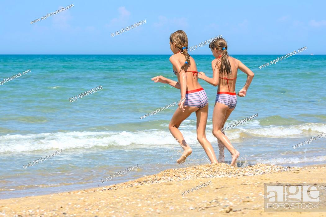 Stock Photo: Two girls run along the shore running into the sea.