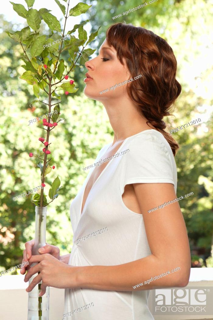 Stock Photo: Young woman smelling plant.