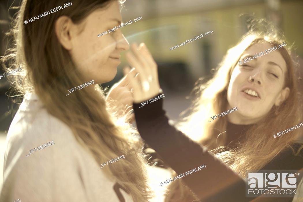 Stock Photo: woman slapping friendly man in face, outside in sunlight, in Berlin, Germany.