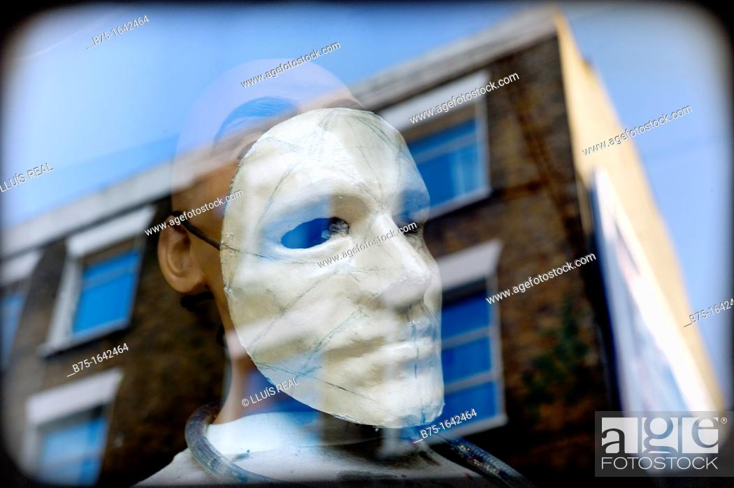Stock Photo: Female mannequin with a mask in shop-window glass with reflections.