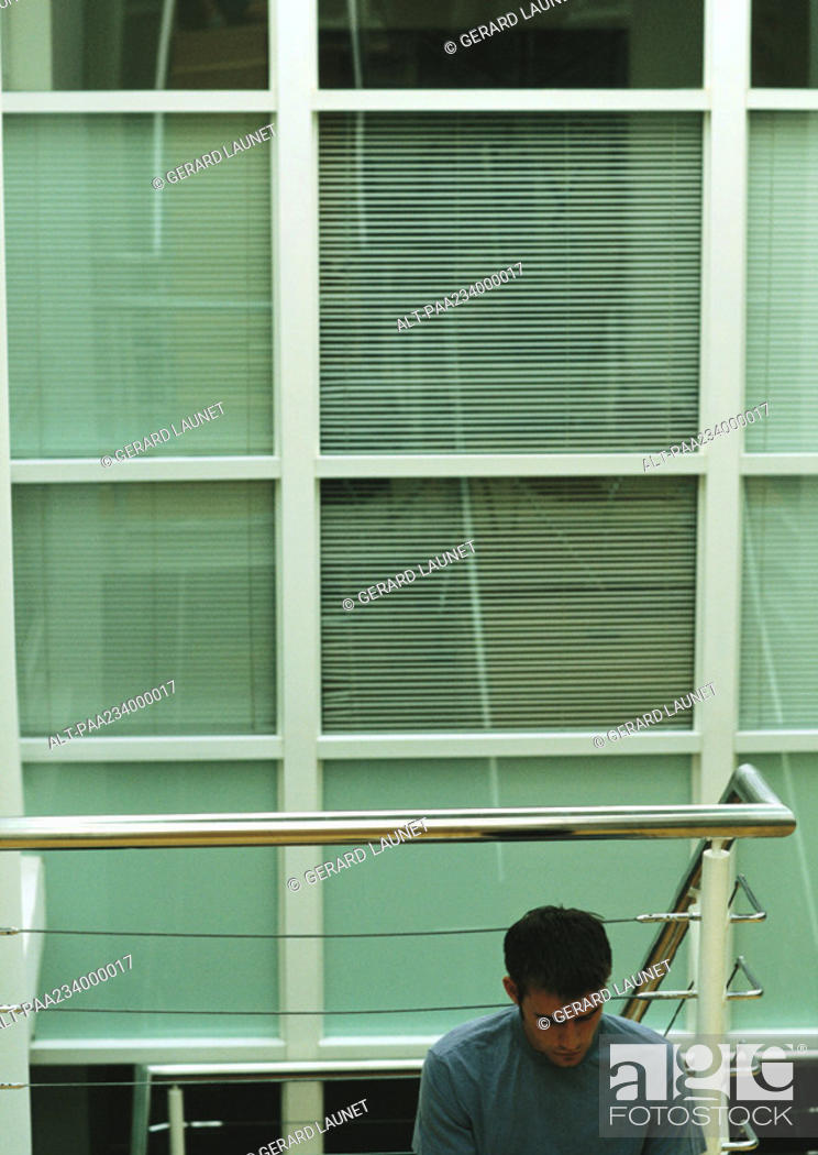 Stock Photo: Man sitting, leaning against metal rails, window in background.