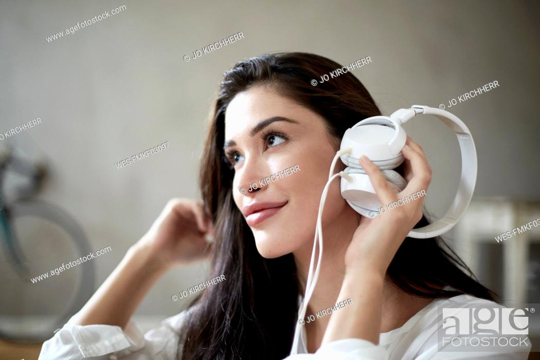 Stock Photo: Smiling woman holding white headphones listening music.