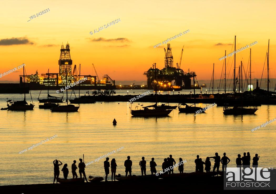 Stock Photo: Canoists from University club at sunrise on Alcaravaneras beach in Las Palmas, Gran Canaria, Canary Islands, Spain. Drilling ship and rig undergoing repairs in.