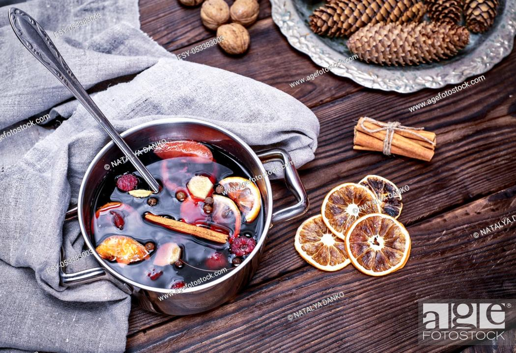 Stock Photo: cooked in a steel pan of mulled wine with spices and fruits on a brown wooden background, top view.