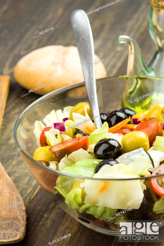 Photo de stock: Vertical making glass bowl with lettuce and tomato salad olives.