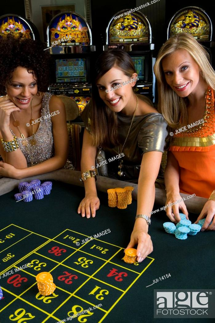 Stock Photo: Woman and friends placing gambling chips on roulette table, portrait, elevated view.