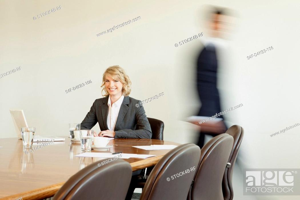 Stock Photo: Businesswoman in conference room with person in background passing by, Munich, Bavaria, Germany.