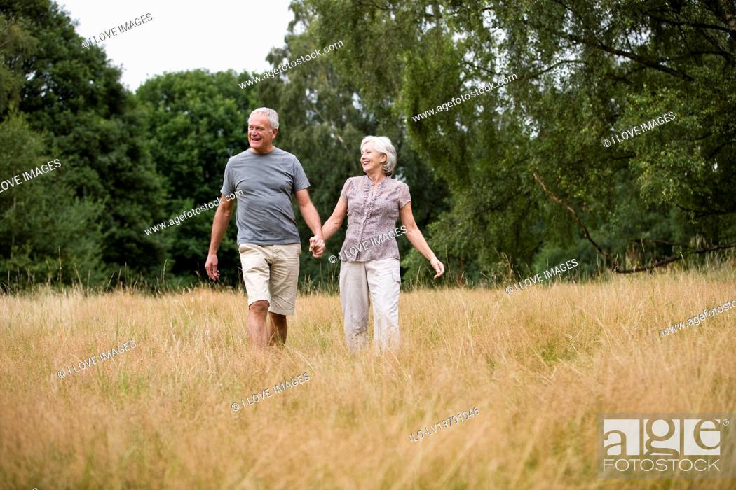 Stock Photo: A senior couple walking through a field, holding hands.