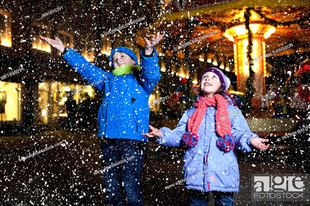 Stock Photo: Children catching snow at Christmas Market in Bad Toelz, Bavaria, Germany.