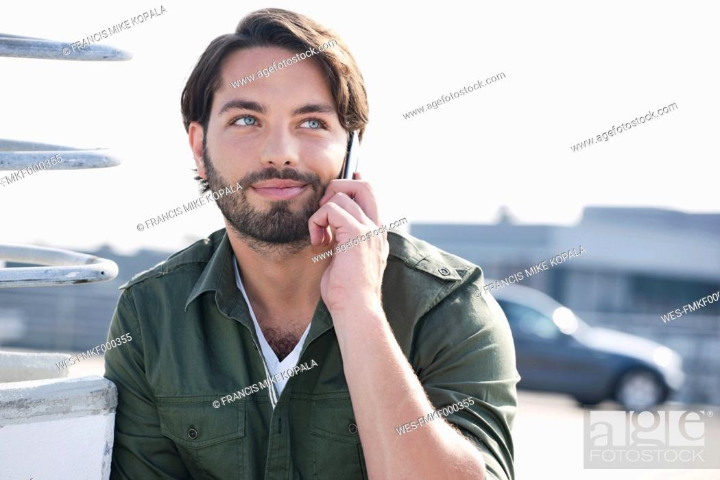 Stock Photo: Germany, Cologne, Young man on phone, smiling.