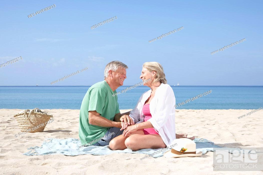 Stock Photo: Spain, Senior couple sitting on beach.