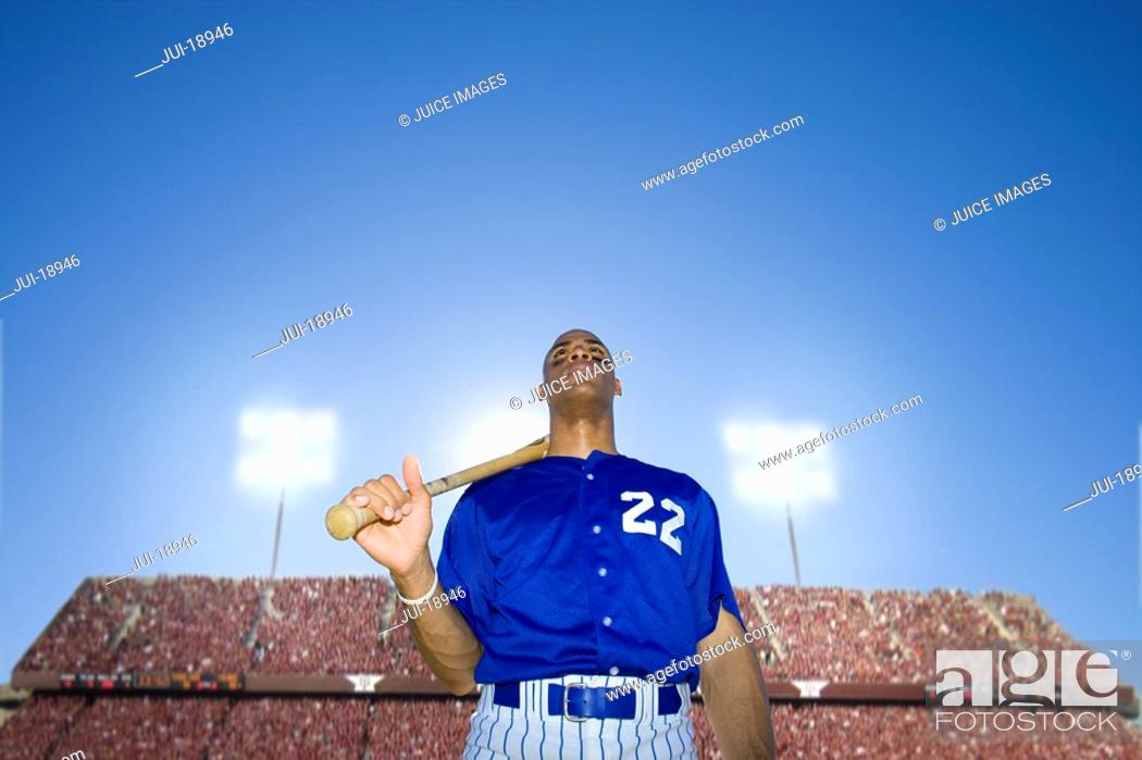 Stock Photo: Baseball player holding bat with crowd in background.