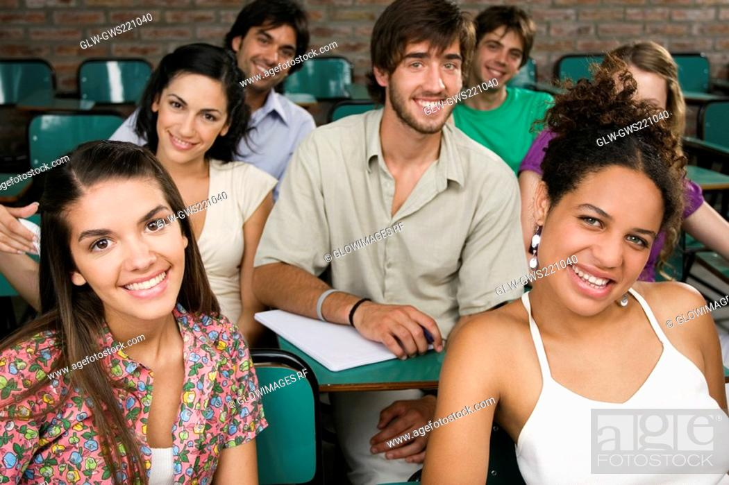 Stock Photo: Portrait of university students sitting in a classroom and smiling.