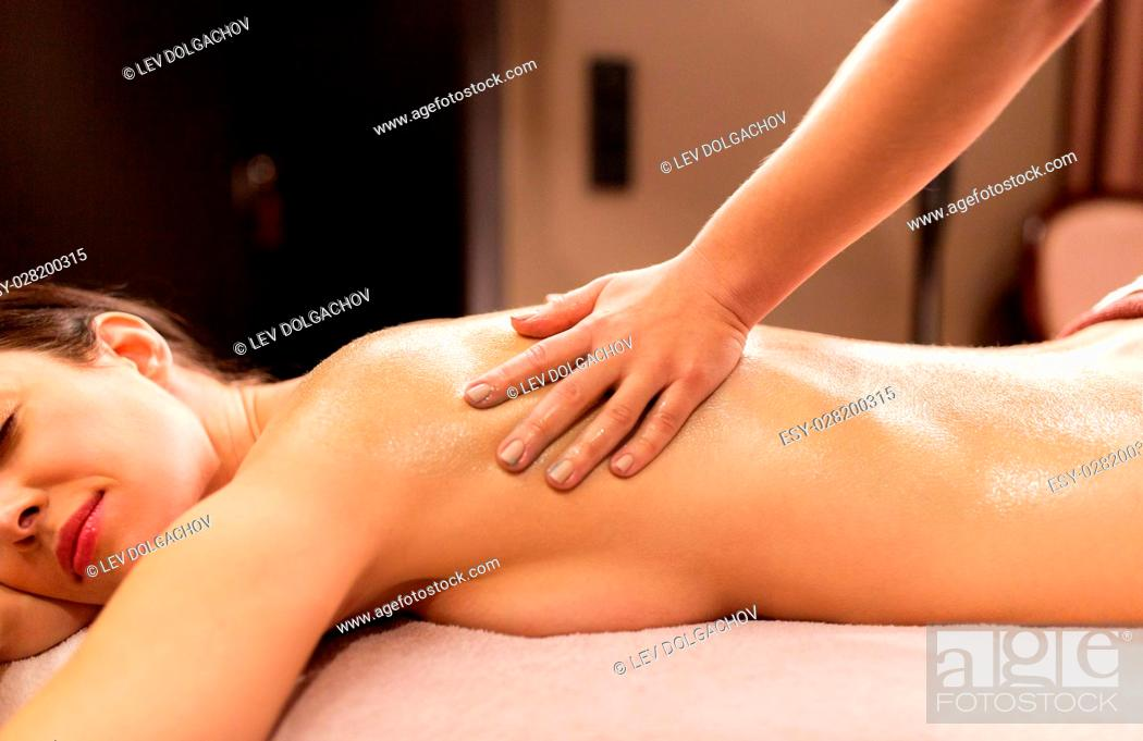 Stock Photo: people, beauty, healthy lifestyle and relaxation concept - beautiful young woman lying and having back massage at spa.