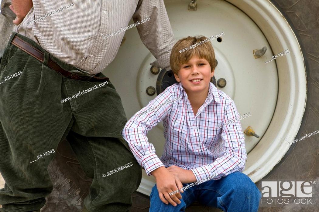 Stock Photo: Boy sitting on rim of tractor wheel.