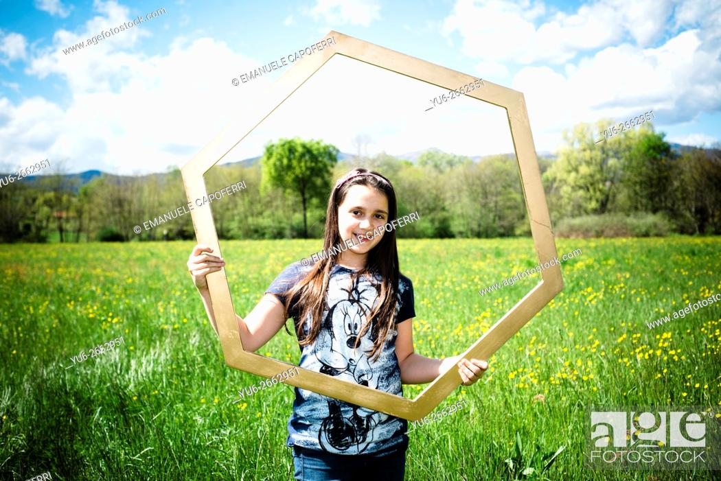 Stock Photo: Girl of 10 years with large hexagonal frame, in the middle of a green meadow.