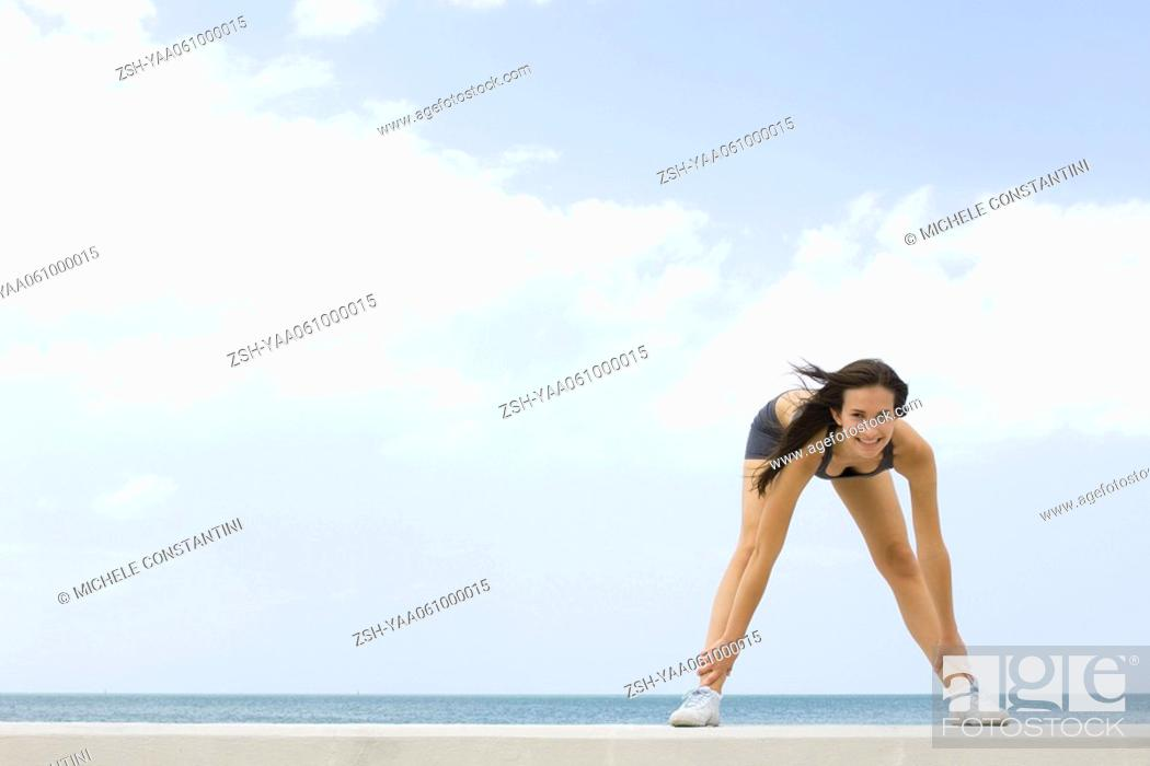 Stock Photo: Young woman bending over, touching ankles, smiling at camera.