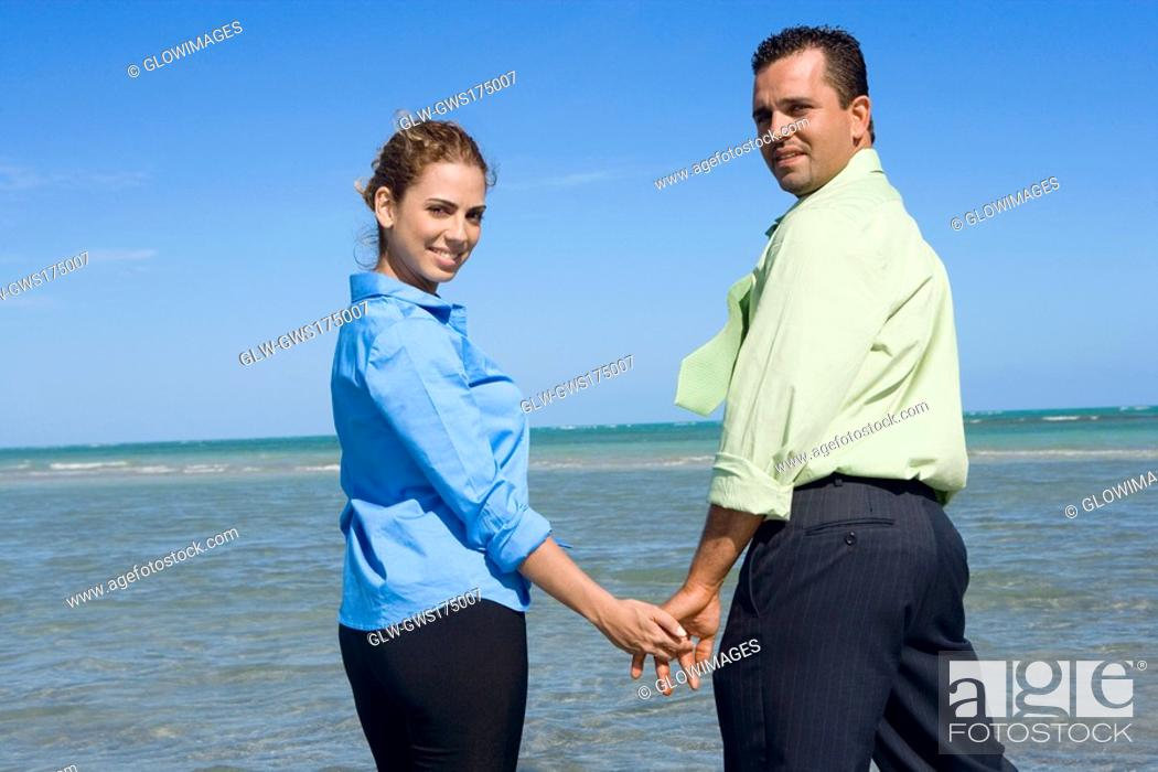 Stock Photo: Portrait of a mid adult couple standing on the beach with holding their hands.