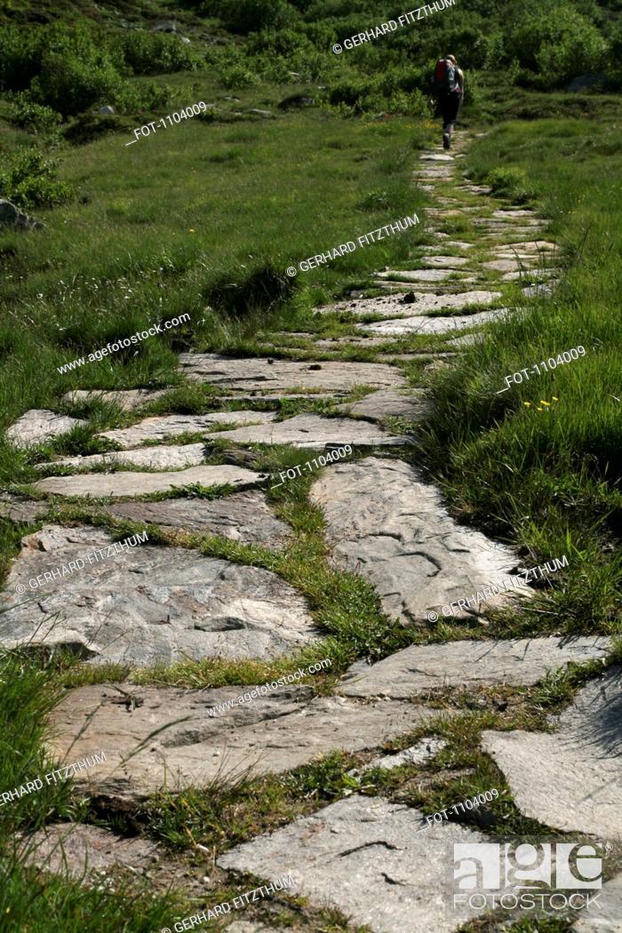 Stock Photo: A hiker on a stone footpath, Binn Valley, Valais Canton, Switzerland.