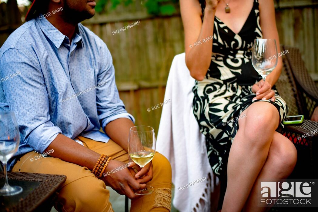 Stock Photo: Man and woman at garden party, sitting, in conversation, holding wine glasses, mid section.