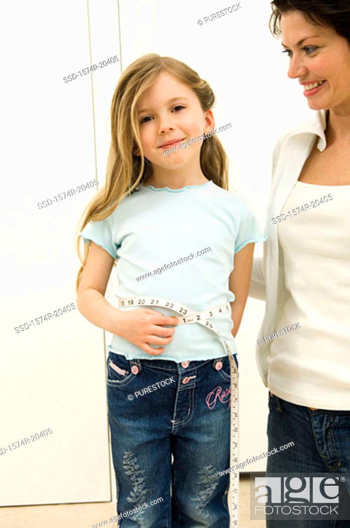 Stock Photo: Portrait of a girl measuring her waist with her mother standing beside her.