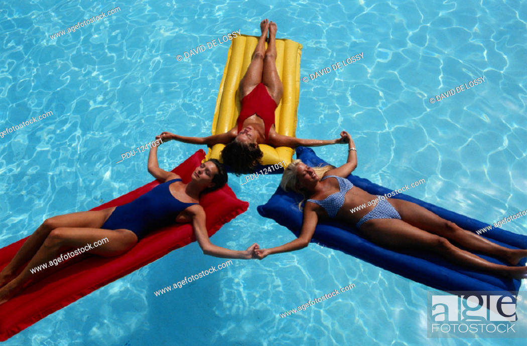 Stock Photo: Woman on pool rafts, elevated view.