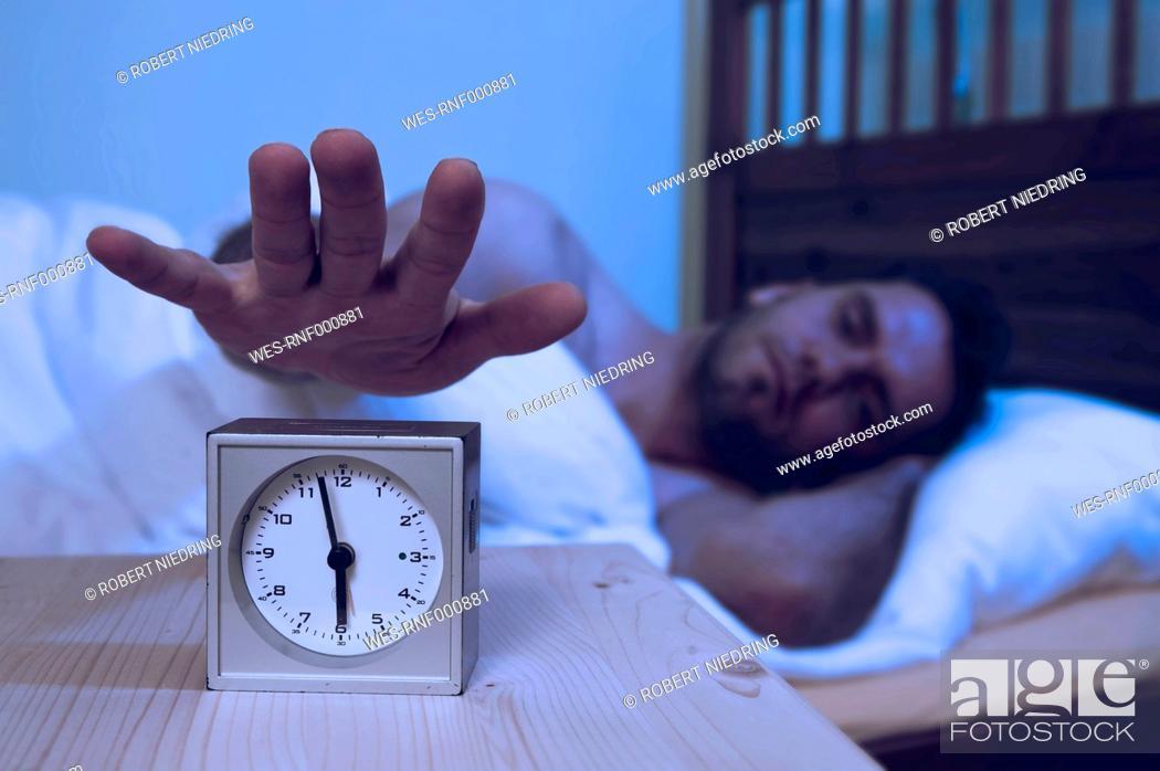 Stock Photo: Man turning off alarm clock.