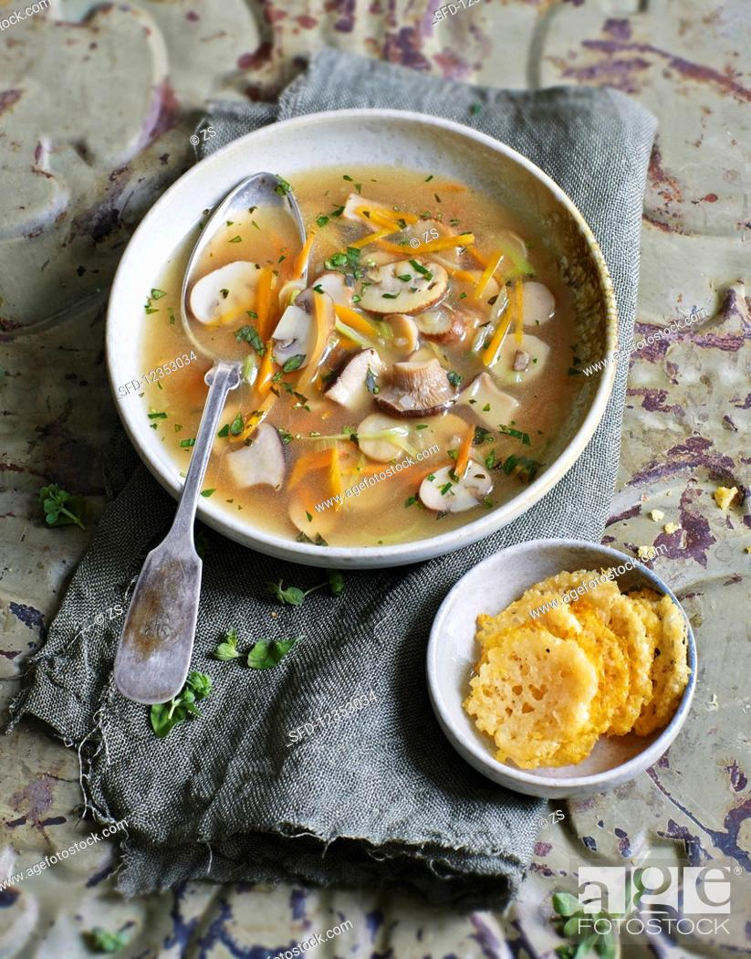Stock Photo: Clear mushroom soup with parmesan crisps.