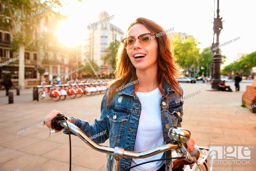 Stock Photo: Photo of young beautiful woman outdoors on bicycle on the street looking aside.