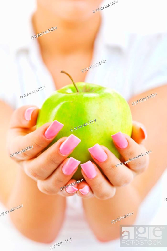 Stock Photo: Young woman eating green apple isolated on white background.