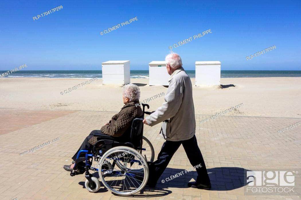 Stock Photo: Retired husband taking disabled elderly wife in wheelchair for a walk on promenade along the coast on a cold sunny day in spring.