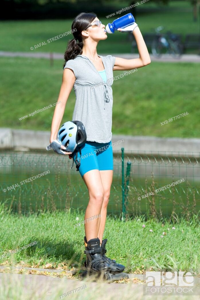 Imagen: Young woman wearing rollerblades in park.