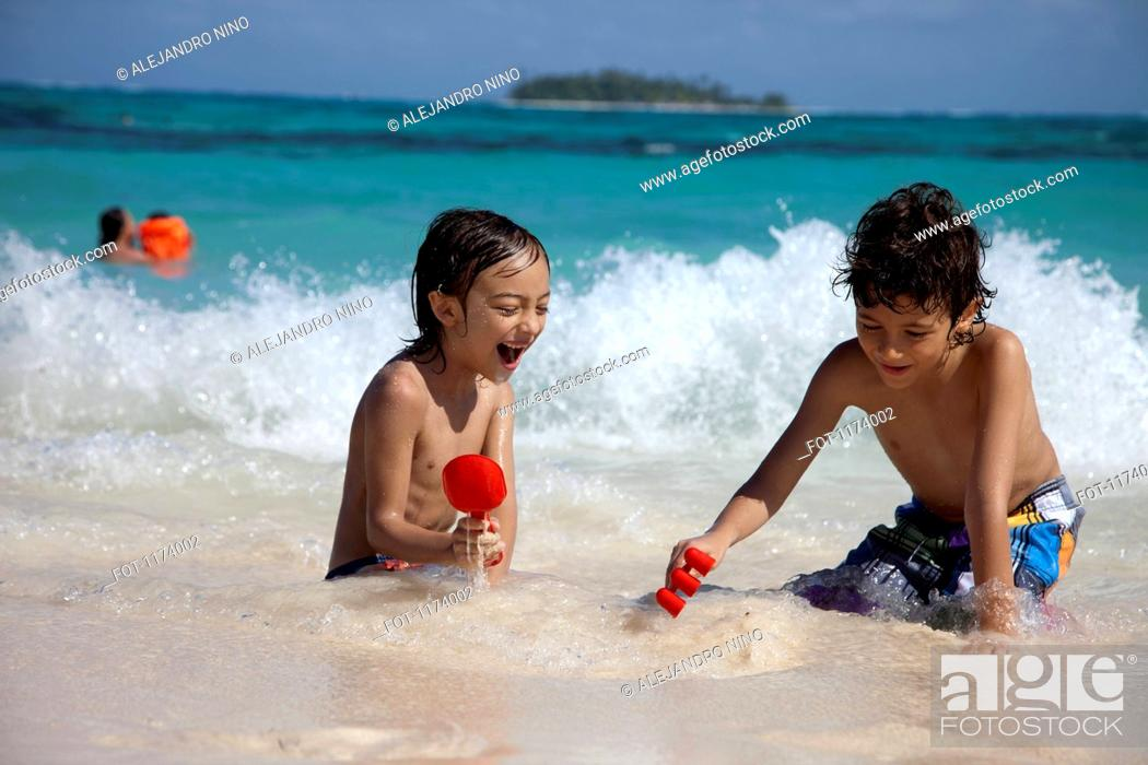 Stock Photo: Two boys playing in the surf,.