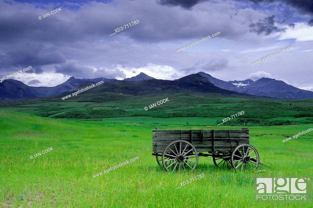 Stock Photo: Old wagon and Rocky Mountains near Twin Butte, Alberta Canada.