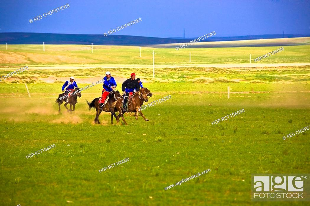 Stock Photo: Four people horseback riding in a field, Inner Mongolia, China.
